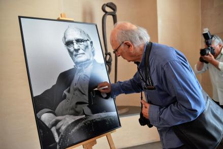 Carlos Saura firmando su retrato